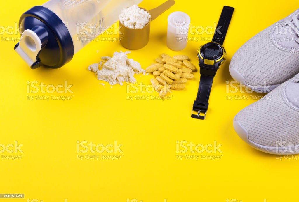 Sports nutrition, proteins and vitamins on a yellow background. stock photo