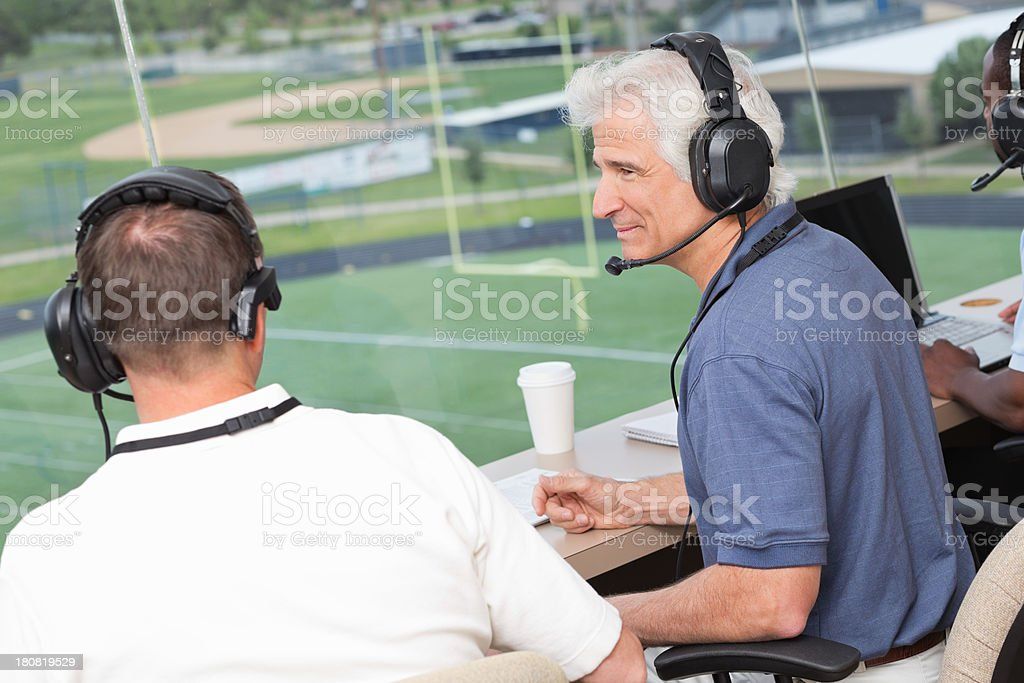 Sports reporters discussing play in press box during football game stock photo