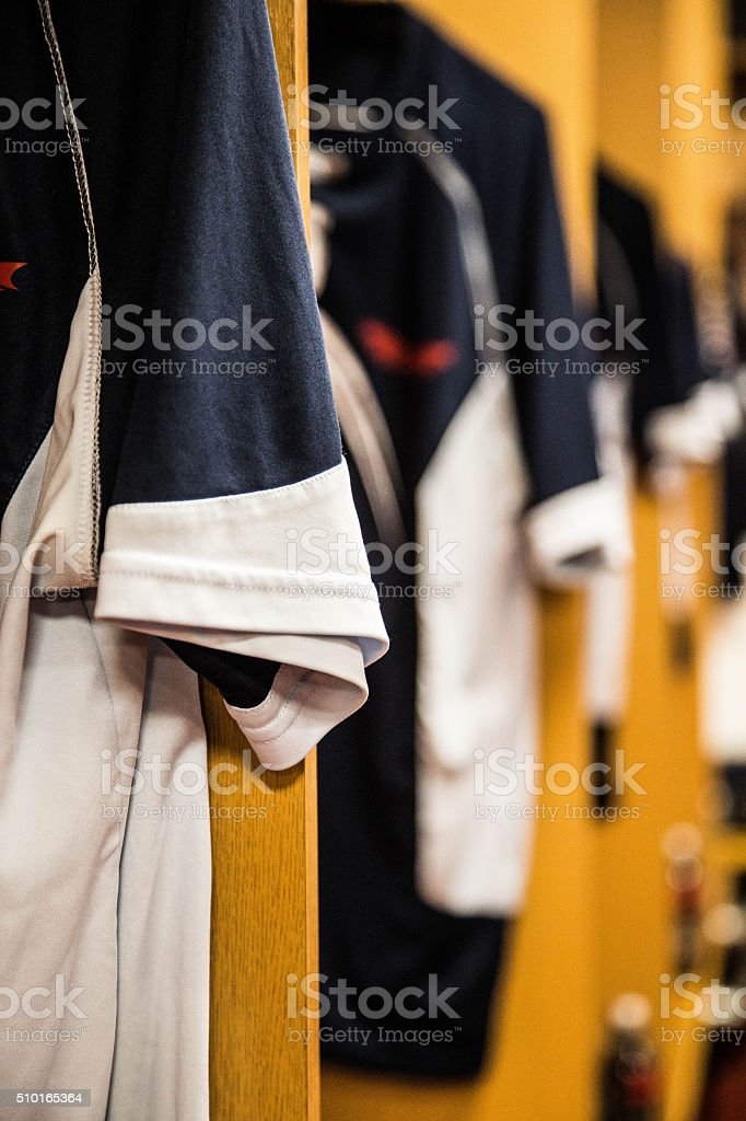 sports shirts hanging in changing rooms stock photo