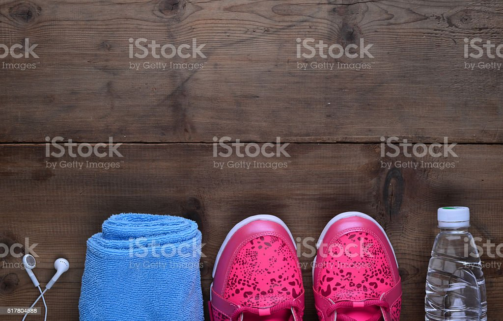 Sports shoes, towels, headphones, alarm clock, cell phone on board stock photo