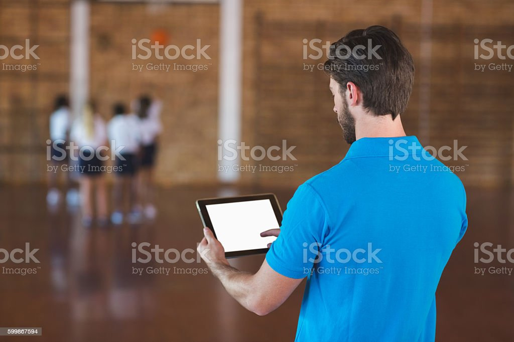 Sports teacher using digital tablet stock photo