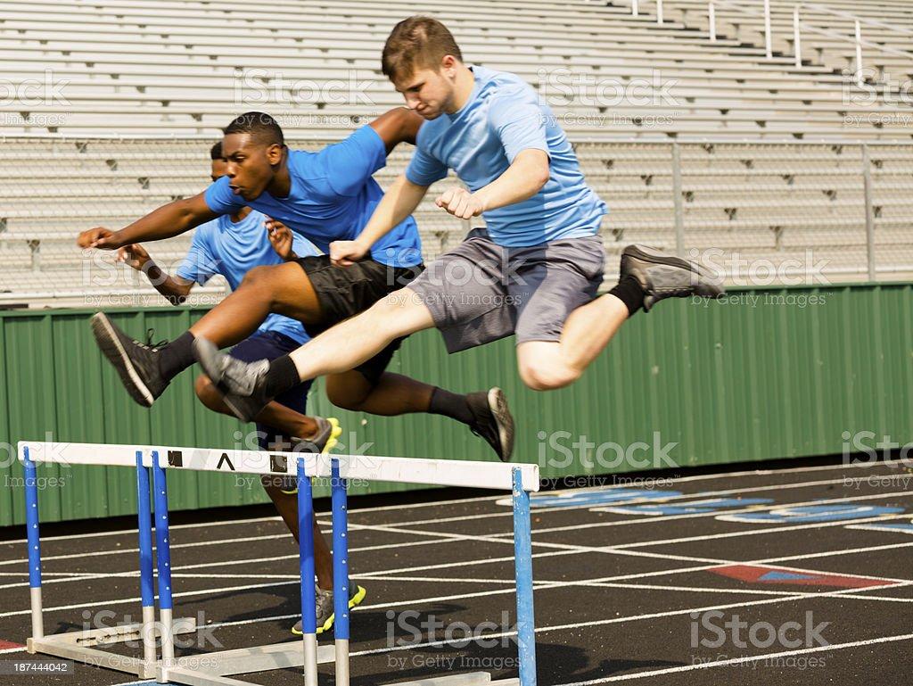 Sports: Three high school boys run a hurdles race. stock photo