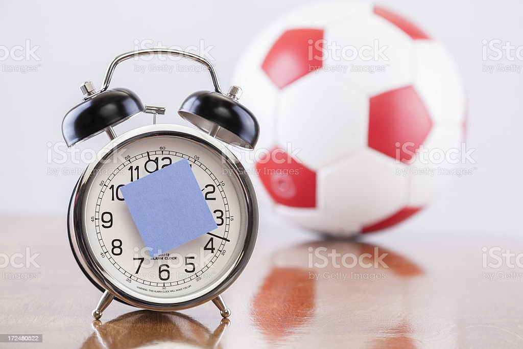 Sports Time:  Alarm clock with blank reminder note.  Ball background. stock photo