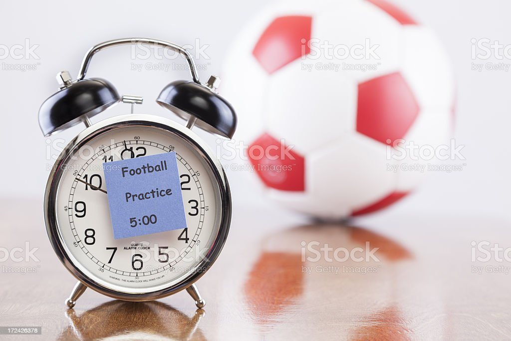 Sports Time:  Alarm clock with football practice reminder.  Ball background. stock photo