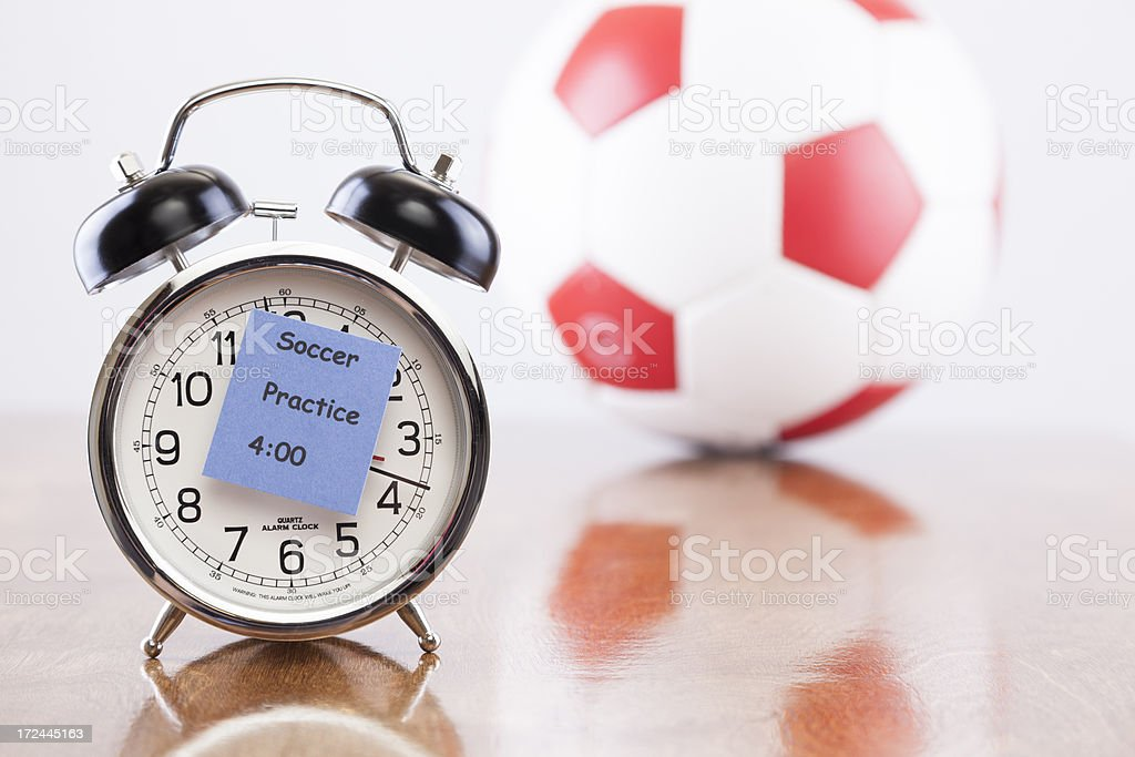Sports Time:  Alarm clock with soccer practice reminder. Ball background stock photo