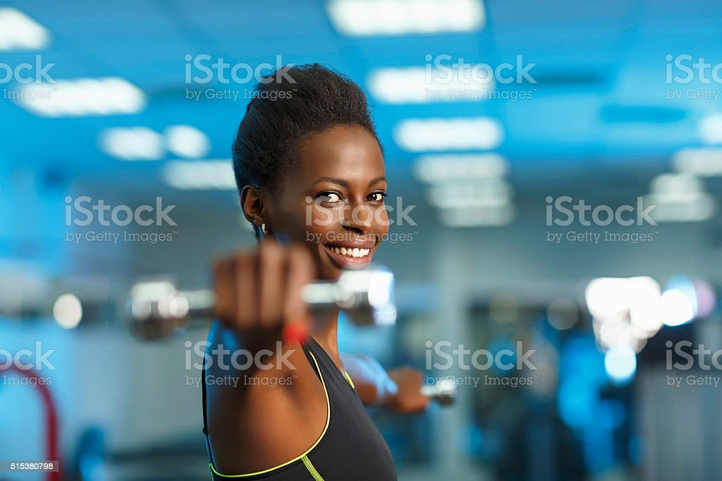 Sports training  Fitness Woman at the gym lifting dumbbells stock photo