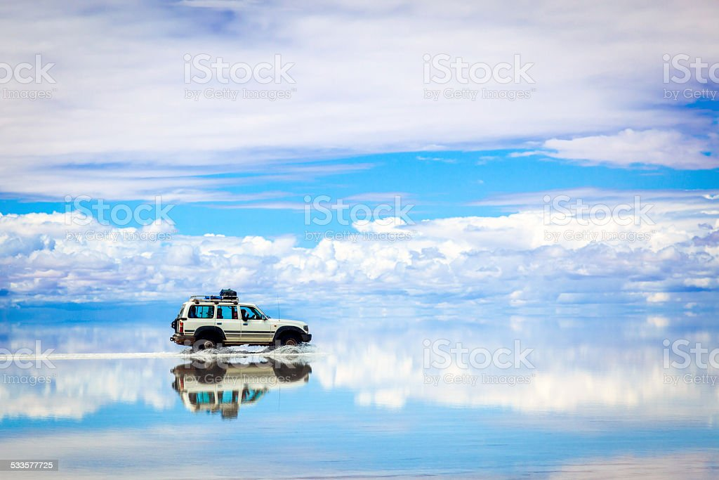 Sports Utility Vehicle driving in the Salar de Uyuni stock photo