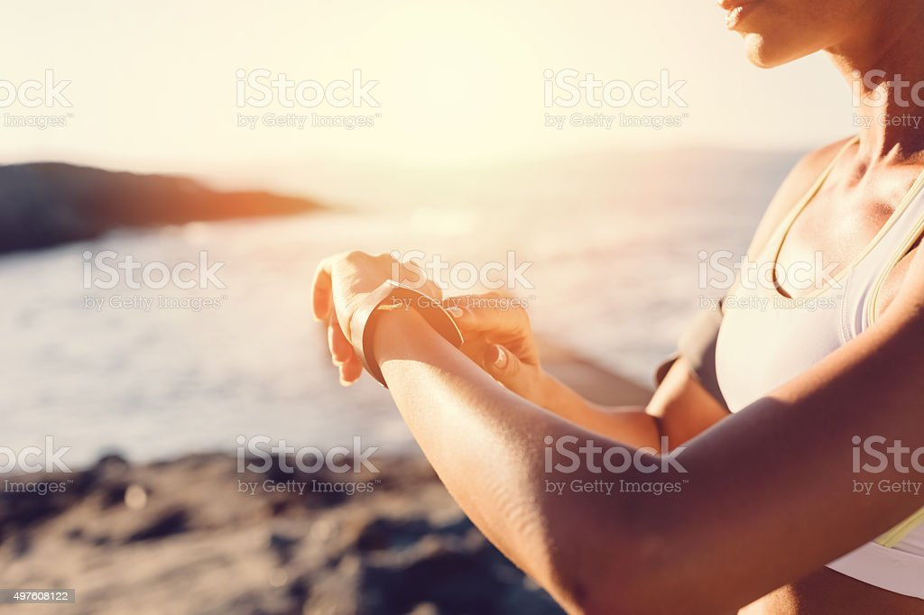 Sports woman at the beach using smart watch stock photo