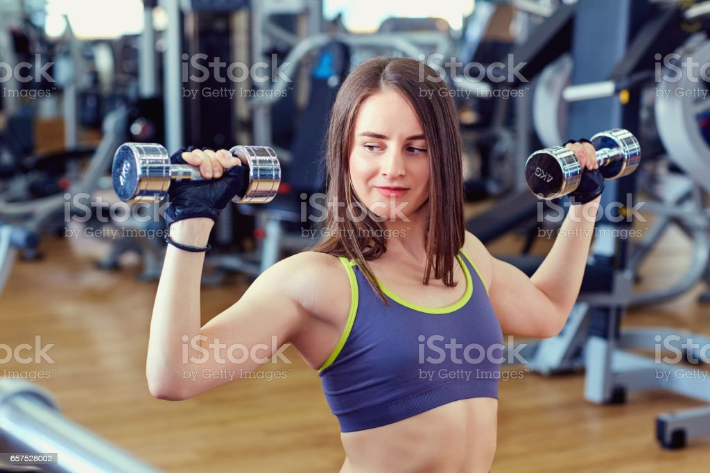 Sports woman athlete with dumbbells in hands  the gym stock photo