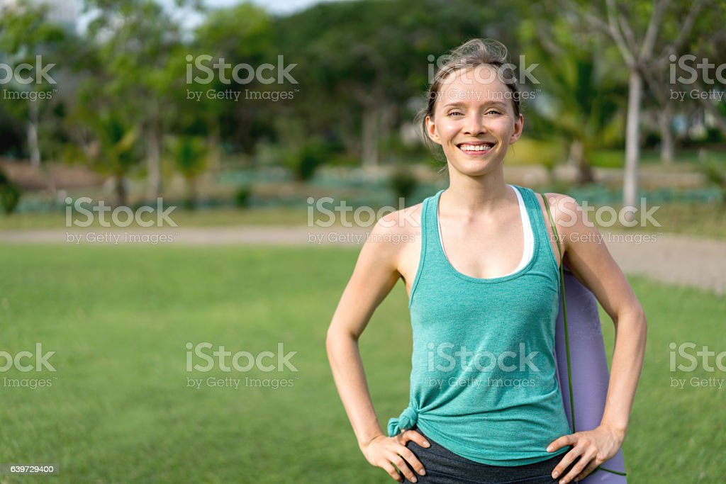 Sports woman carrying her exercise mat stock photo