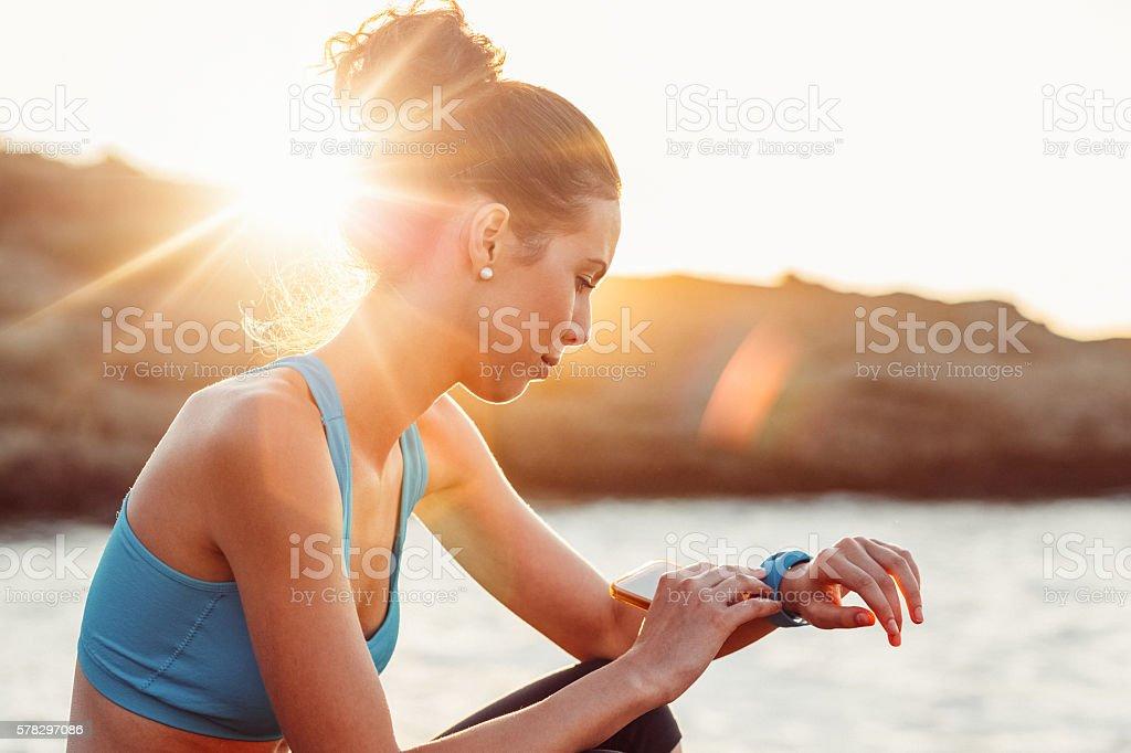 Sports woman checking pulse on smart watch stock photo