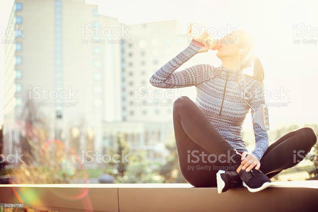 Sports woman drinking water stock photo