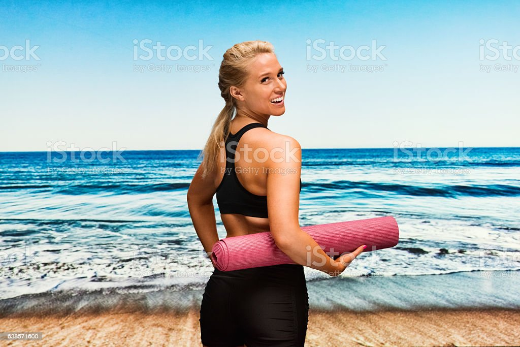 Sports woman holding exercising mat at the beach stock photo