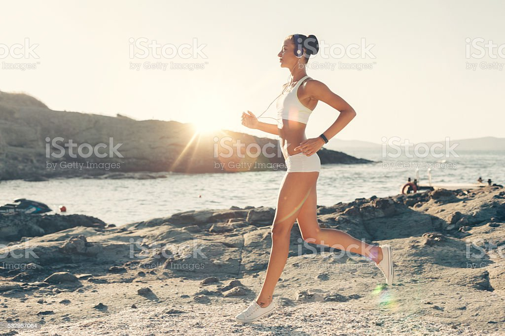 Sports woman jogging at the beach stock photo