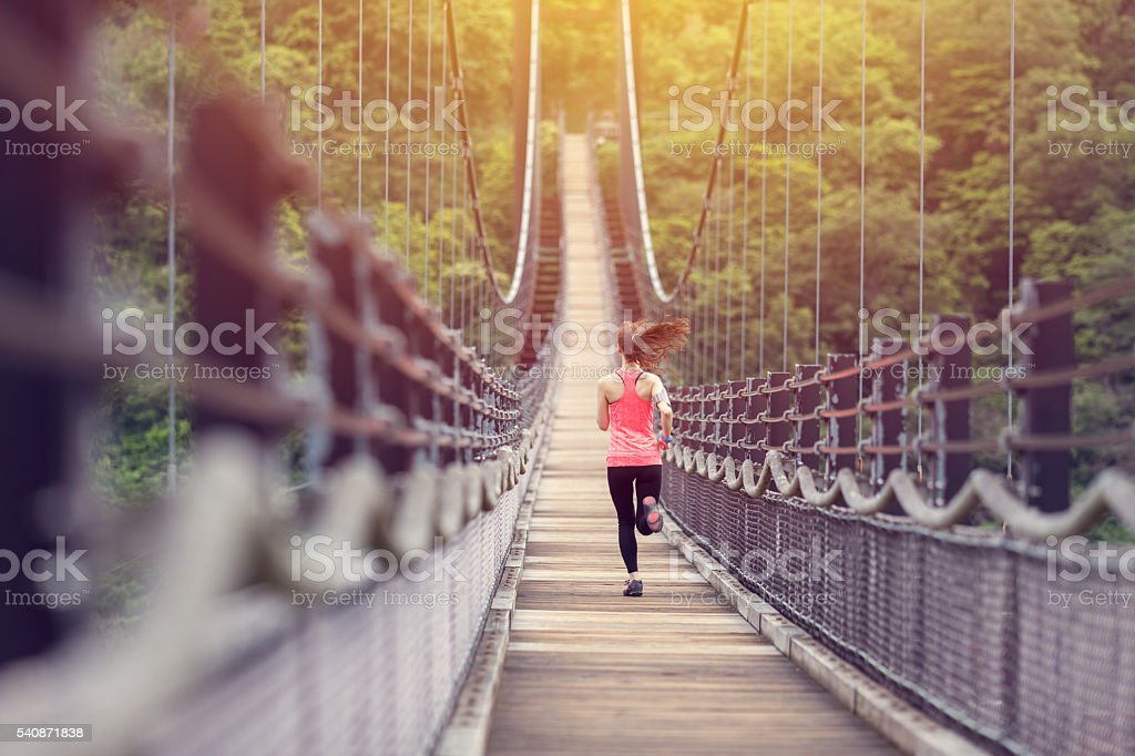 Sports woman jogging at the bridge stock photo