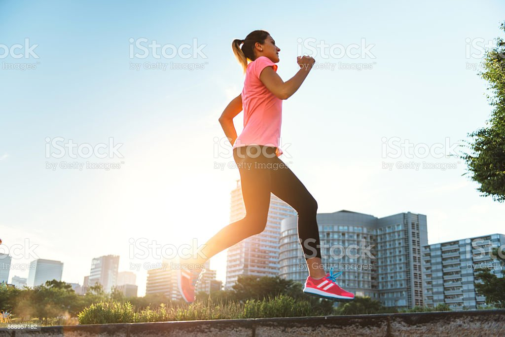 Sports woman jogging in sunset in city of Osaka, Japan stock photo
