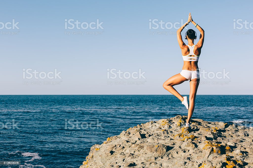 Sports woman meditating at the beach stock photo