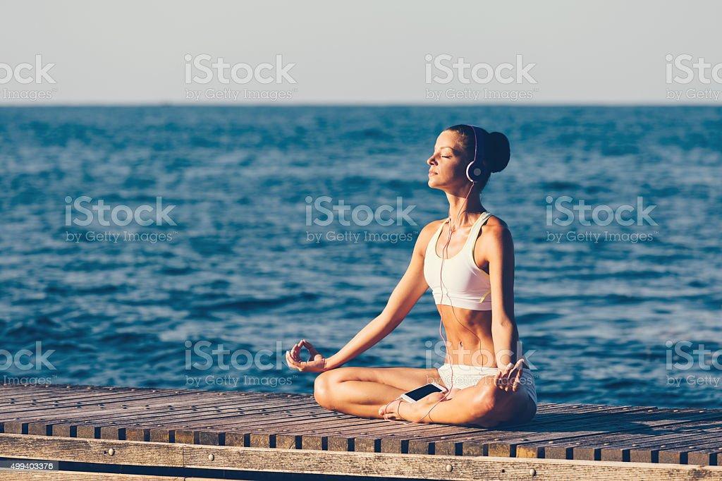 Sports woman meditating at the quay stock photo