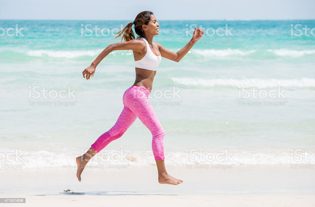Sports woman running at the beach stock photo