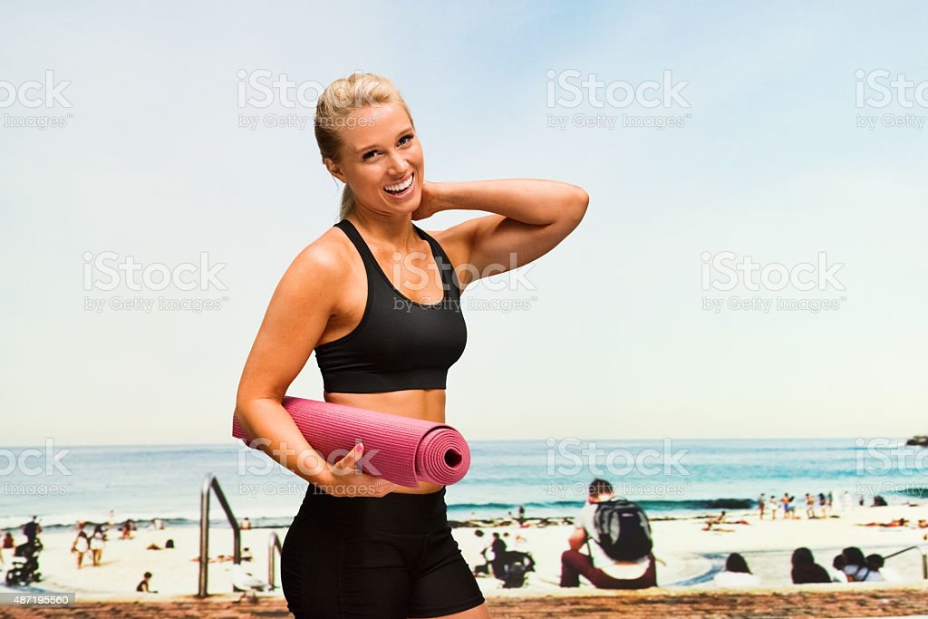 Sports woman with exercise mat standing at beach stock photo