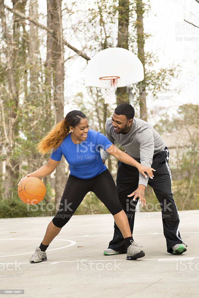 Sports: Young African descent couple play basketball at park. stock photo