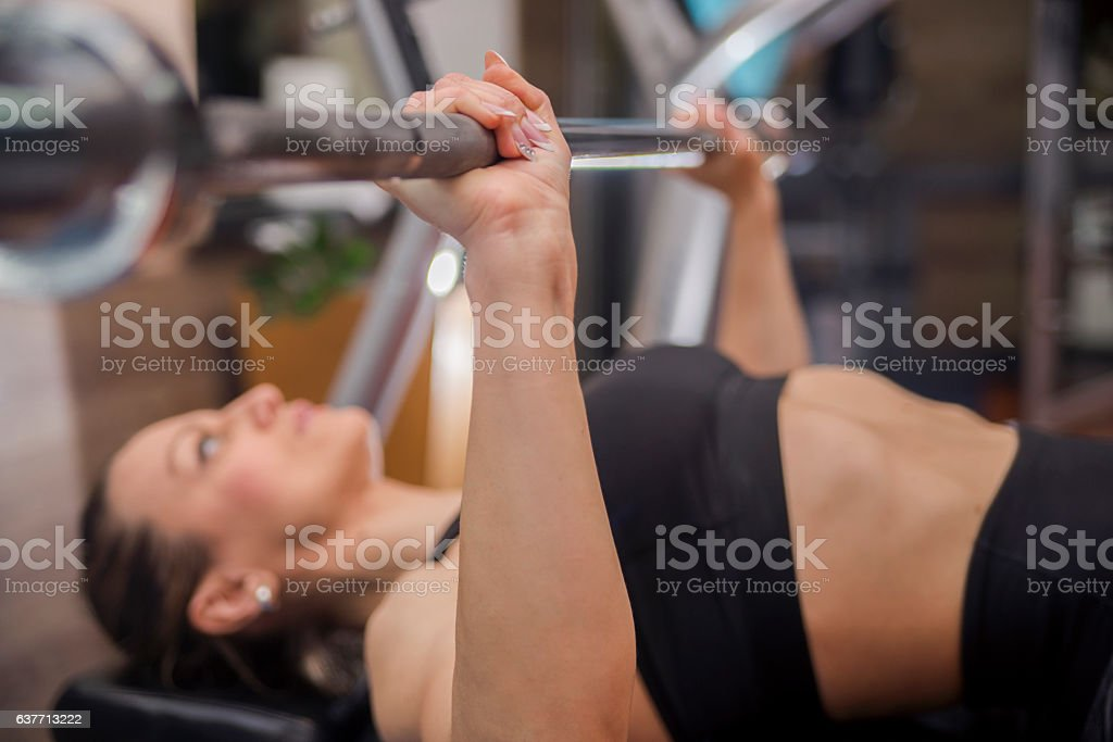 Sports young woman doing exercises with barbell on bench stock photo