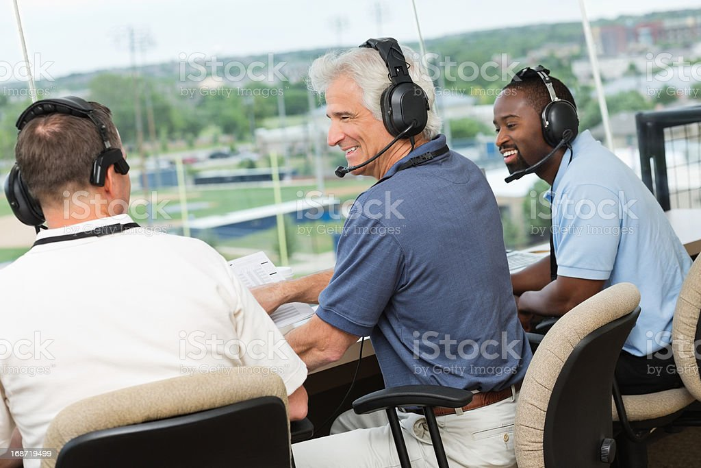 Sportscasters discussing sports game in a press box stock photo