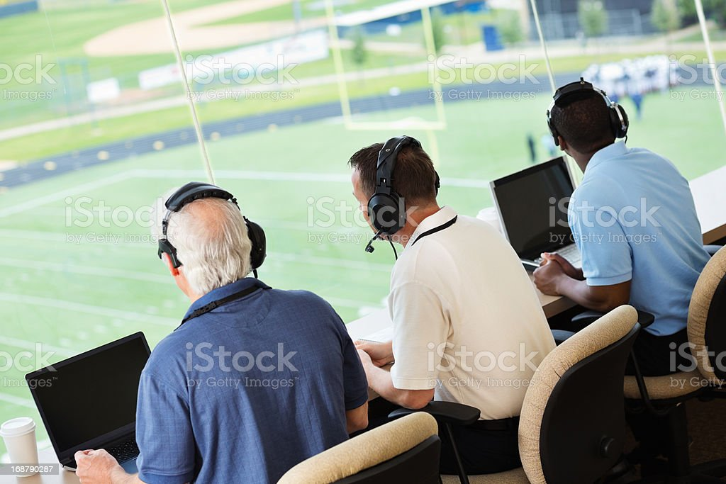 Sportscasters watching and calling a football game in press box stock photo