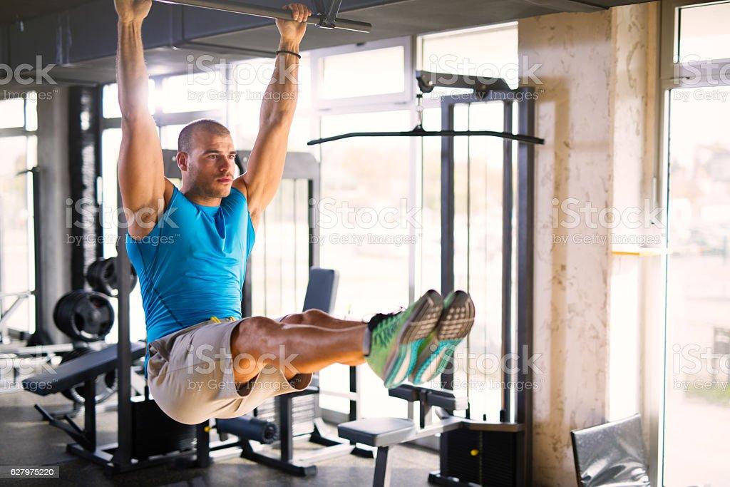 Sportsman doing abs workout on horizontal bar stock photo