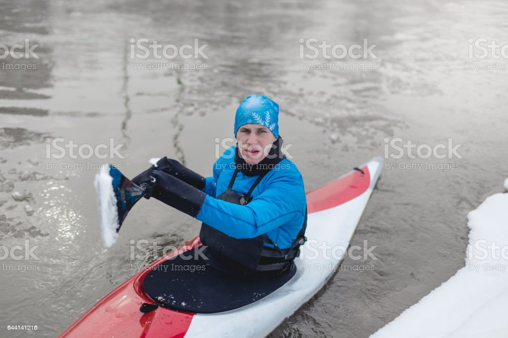 Sportsman driving kayak on cold weather stock photo