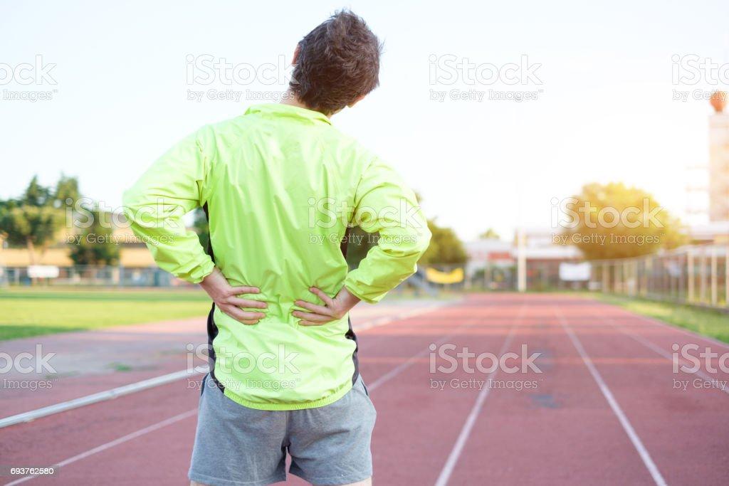 Sportsman feeling backache because of slipped disc stock photo