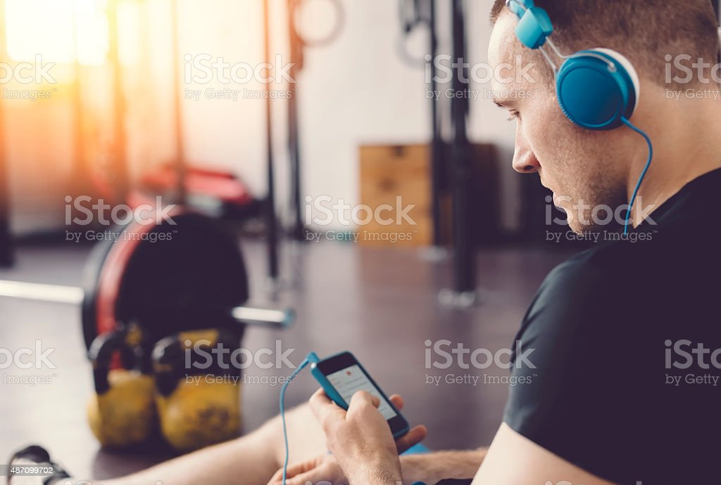 Sportsman in the gym texting on smartphone stock photo