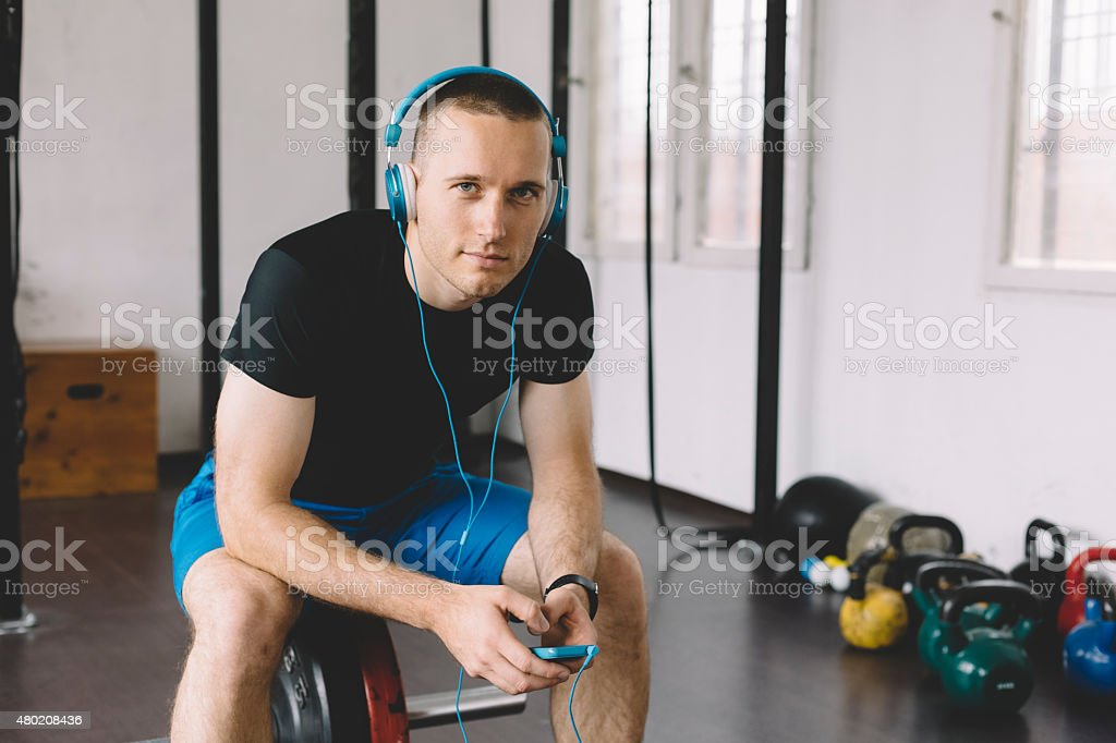 Sportsman listening to the music from smartphone stock photo