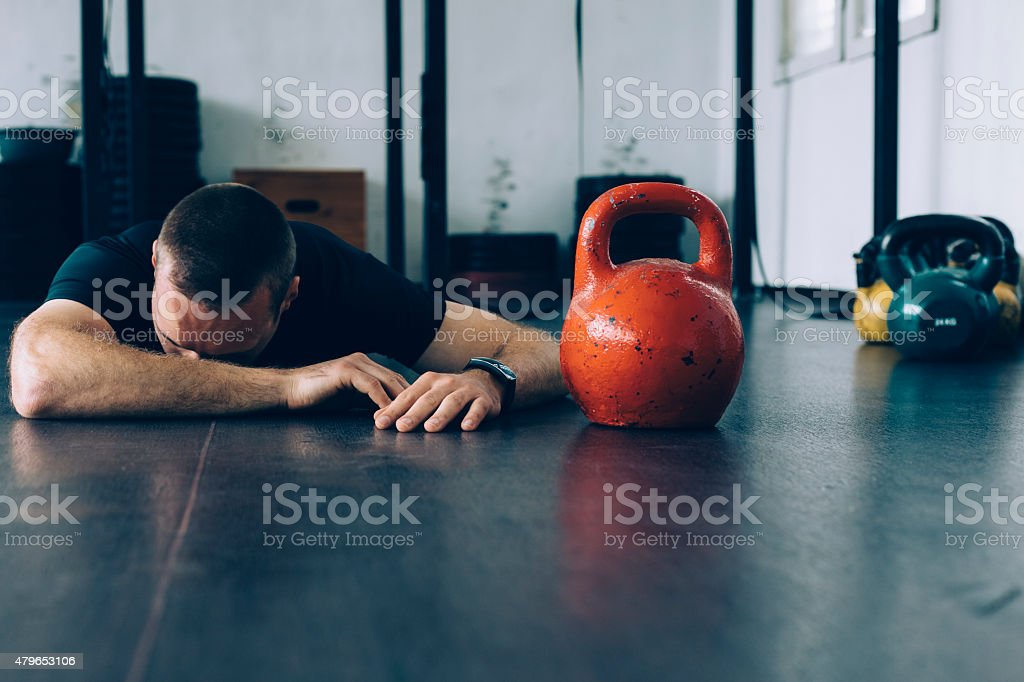 Sportsman lying down on the gym  floor stock photo