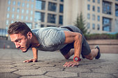 Sportsman making an effort during push-ups on the street.