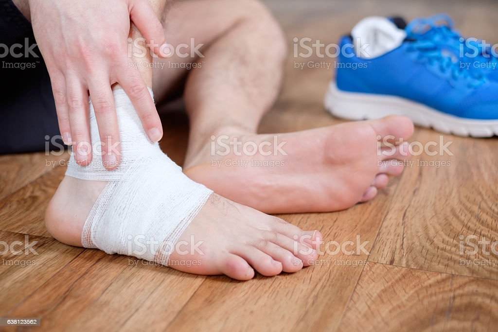 sportsman massaging his injured ankle stock photo