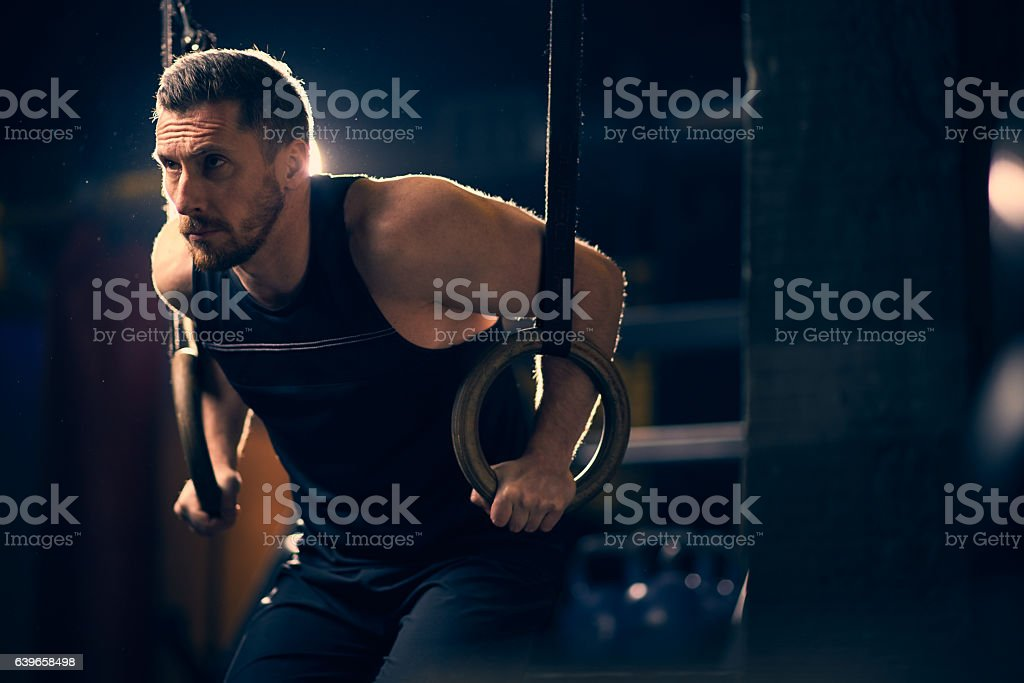 Sportsman performing ring dips in the gym stock photo