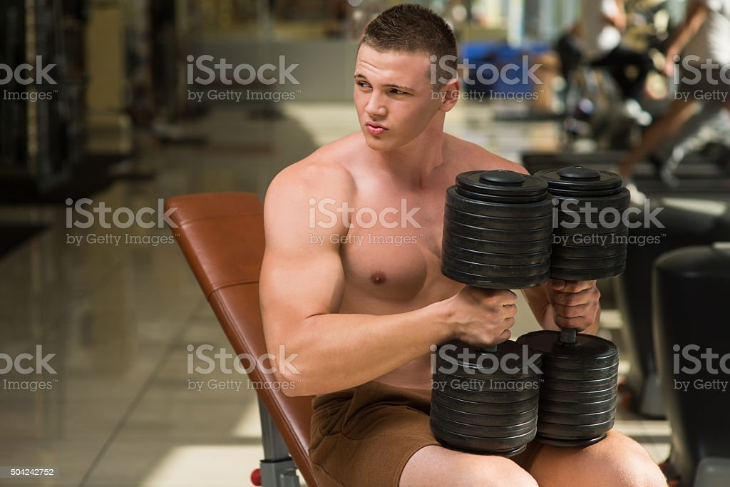 Sportsman posing on camera with dumbbells. stock photo