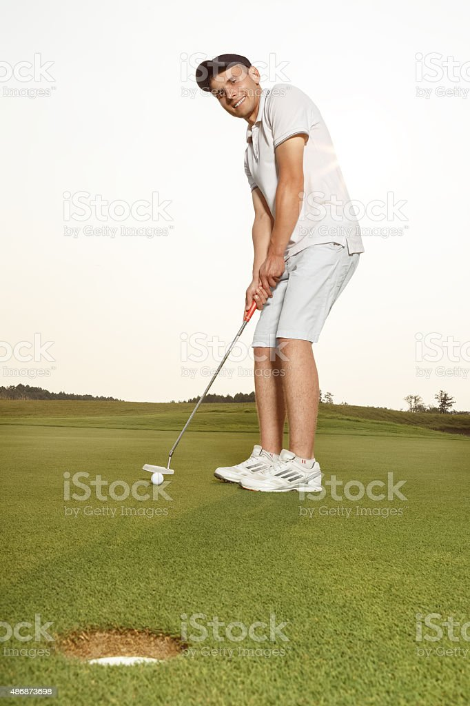 Sportsman putting golf ball into a hole stock photo