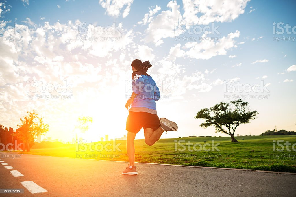 sportsman running in the park in sunset stock photo