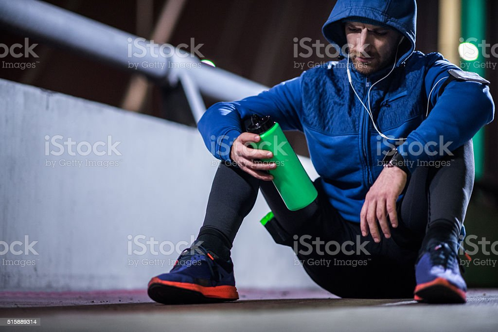 Sportsman sitting on the ground and drinking water stock photo