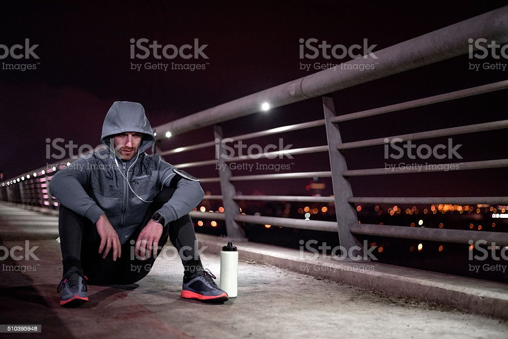 Sportsman sitting on the ground and resting from cardio session stock photo
