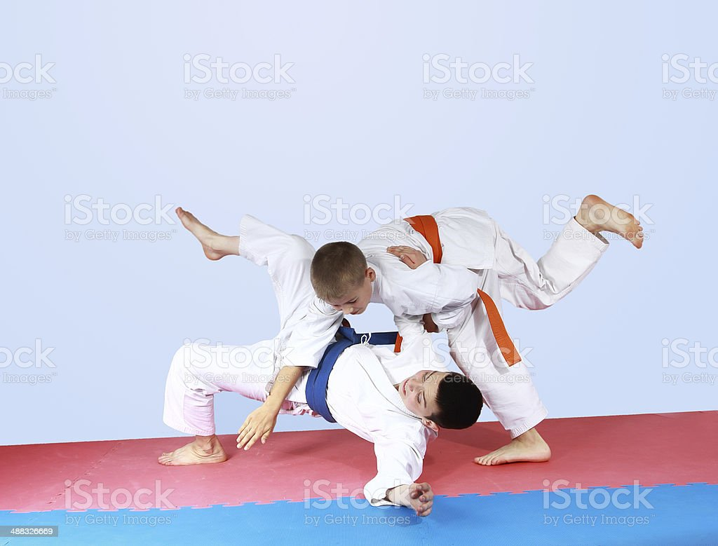 Sportsman with an orange belt threw athlete with a blue belt stock photo