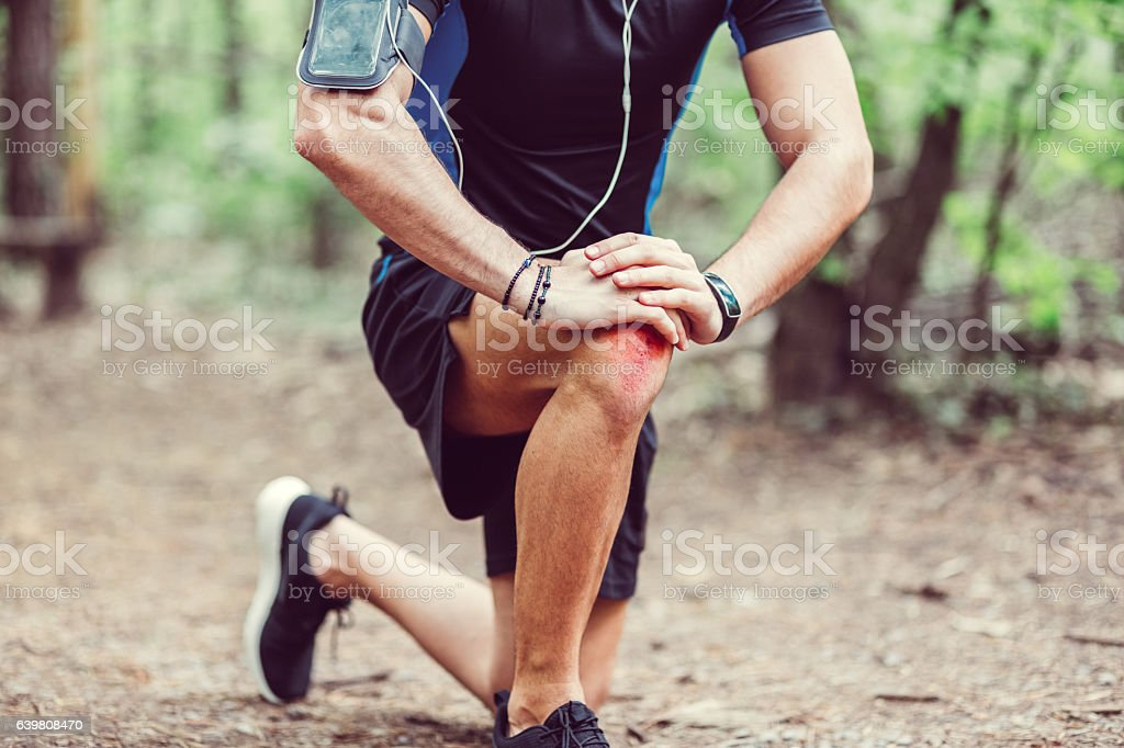 Sportsman with injured knee stock photo