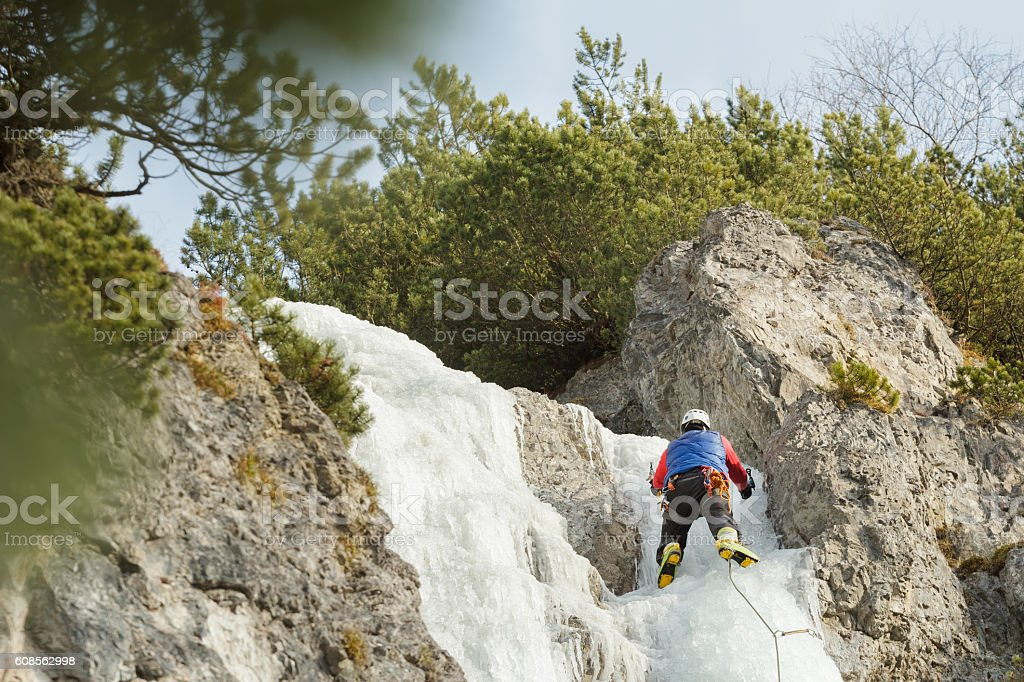 Sportsman working on winter ice climbing route outdoors stock photo