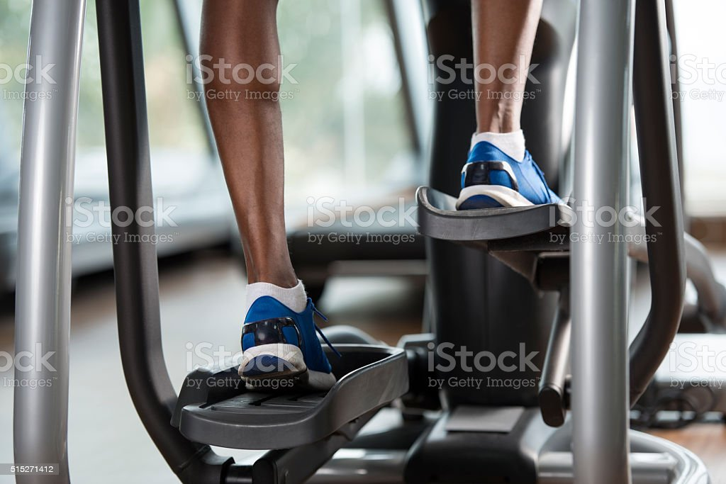 Sportsman's feet on cross-trainer at gym. stock photo