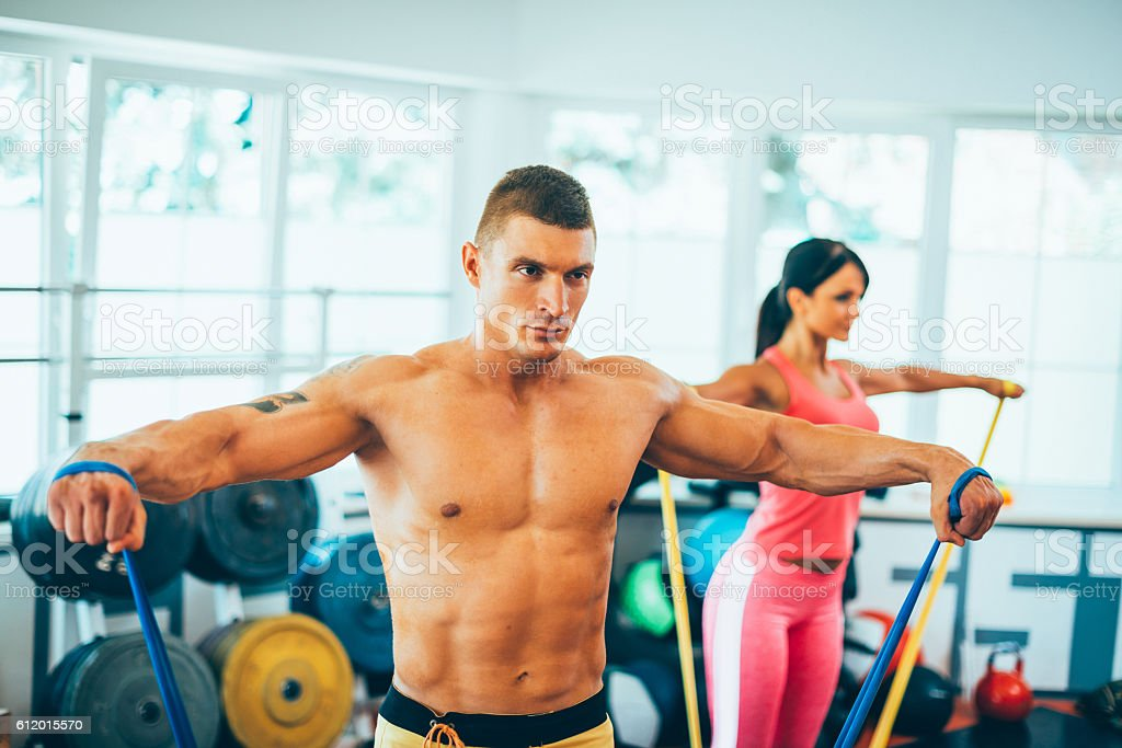 Sportsmen exercising in gym with rubbers stock photo