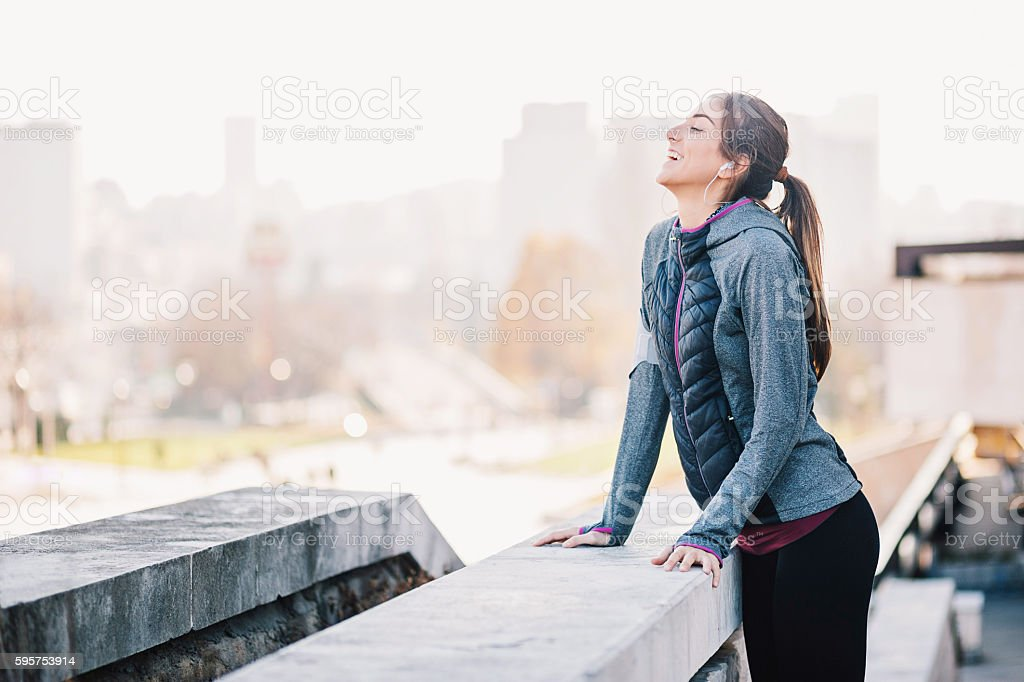 Sportswoman at sunlight with cityscape stock photo