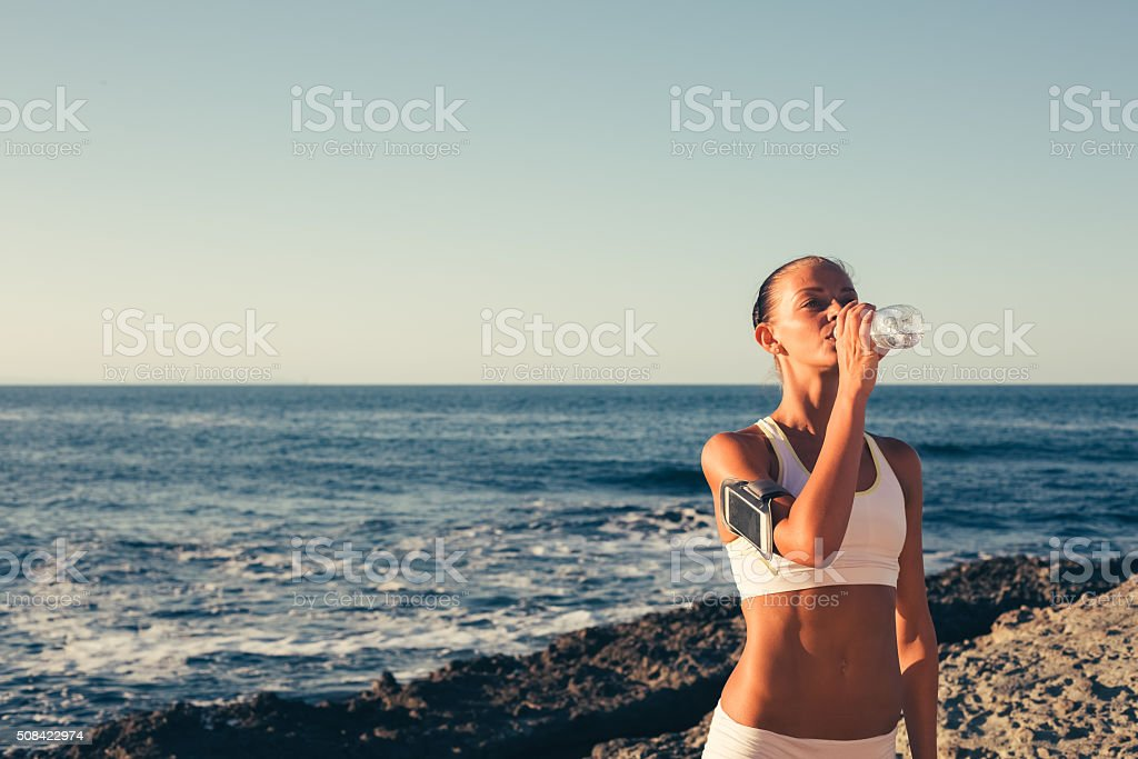 Sportswoman drinking water at the beach stock photo