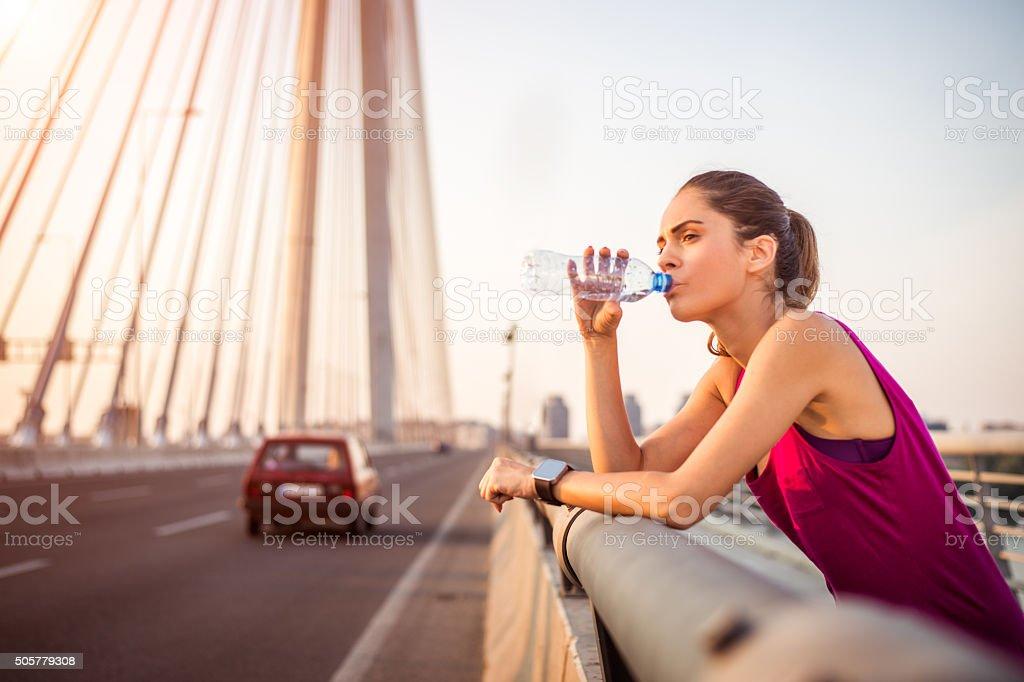 Sportswoman drinking water stock photo